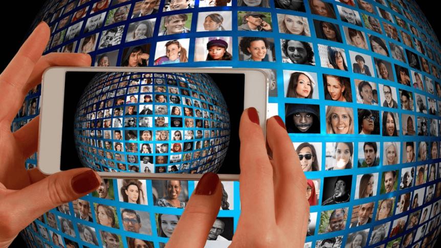 Kuvituskuva, jossa älypuhelimen kautta katsellaan taustalla näkyviä erinäköisiä ihmisiä.